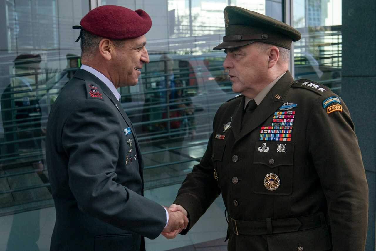 Two men in service uniforms shake hands.