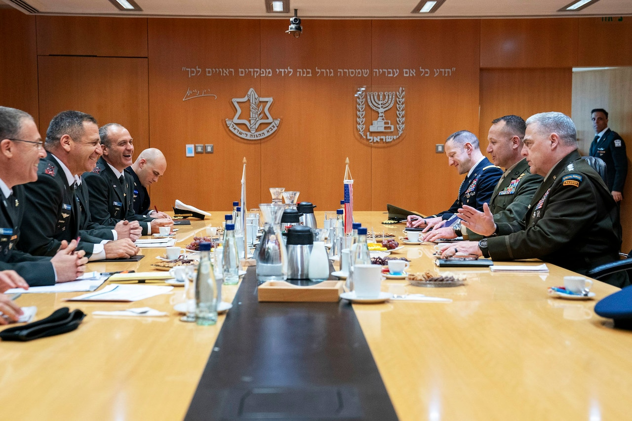 A group of military officers sit around a large table.