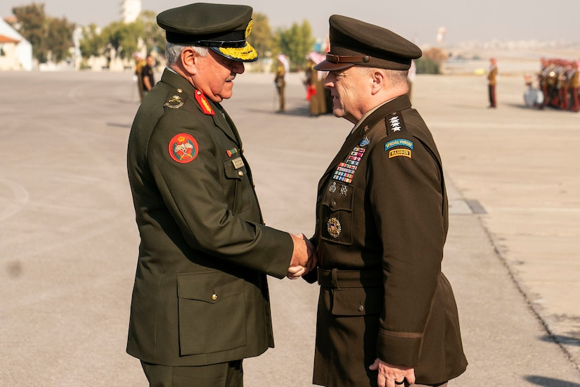 Two military leaders greet each other.