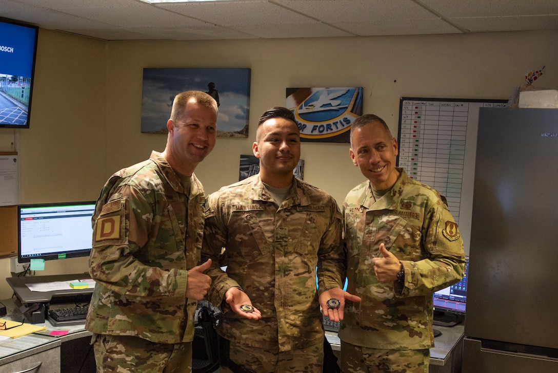Maj. Gen. John Wilcox, Air Force Installation and Mission Support Center commander, and Chief Master Sgt. Edwin Ludwigsen, AFIMSC command chief master sergeant, pose for a photo with Airman Anthony Martinez, 100th Security Forces Squadron base defense operations center controller, after coining him Nov. 22, 2019, at RAF Mildenhall, England. The AFIMSC provides installation and mission support that enables Team Mildenhall to complete its varied mission sets.  (U.S. Air Force photo by Airman 1st Class Joseph Barron)