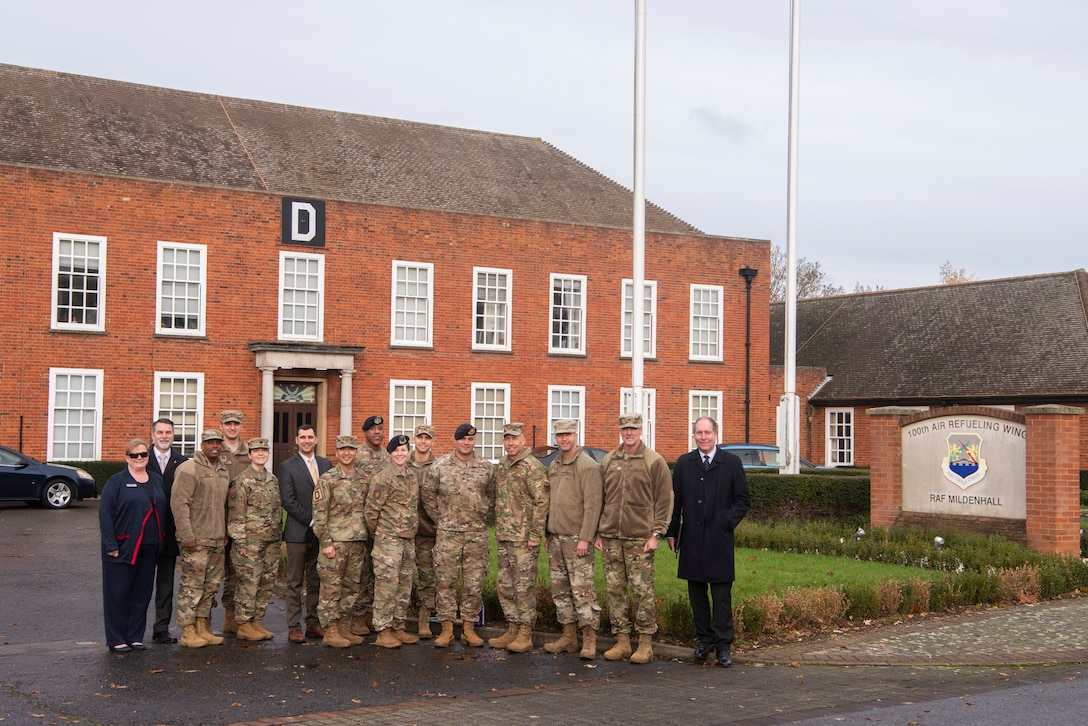 Members of the 100th Air Refueling Wing pose for a photo in front of the wing headquarters with Maj. Gen. John Wilcox, Air Force Installation and Mission Support Center commander, and Chief Master Sgt. Edwin Ludwigsen, AFIMSC command chief master sergeant, Nov. 22, 2019, at RAF Mildenhall, England. The AFIMSC provides installation and mission support that enables Team Mildenhall to complete its varied mission sets. (U.S. Air Force photo by Airman 1st Class Joseph Barron)