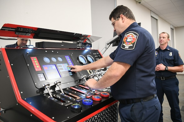 Jason Medina, Fire and Emergency Services (F&ES) driver operator, touches a digital screen on a pump simulator panel that is adorned with handles,dials and gauges, while Daniel Payne, F&ES instructor, observes in the background.