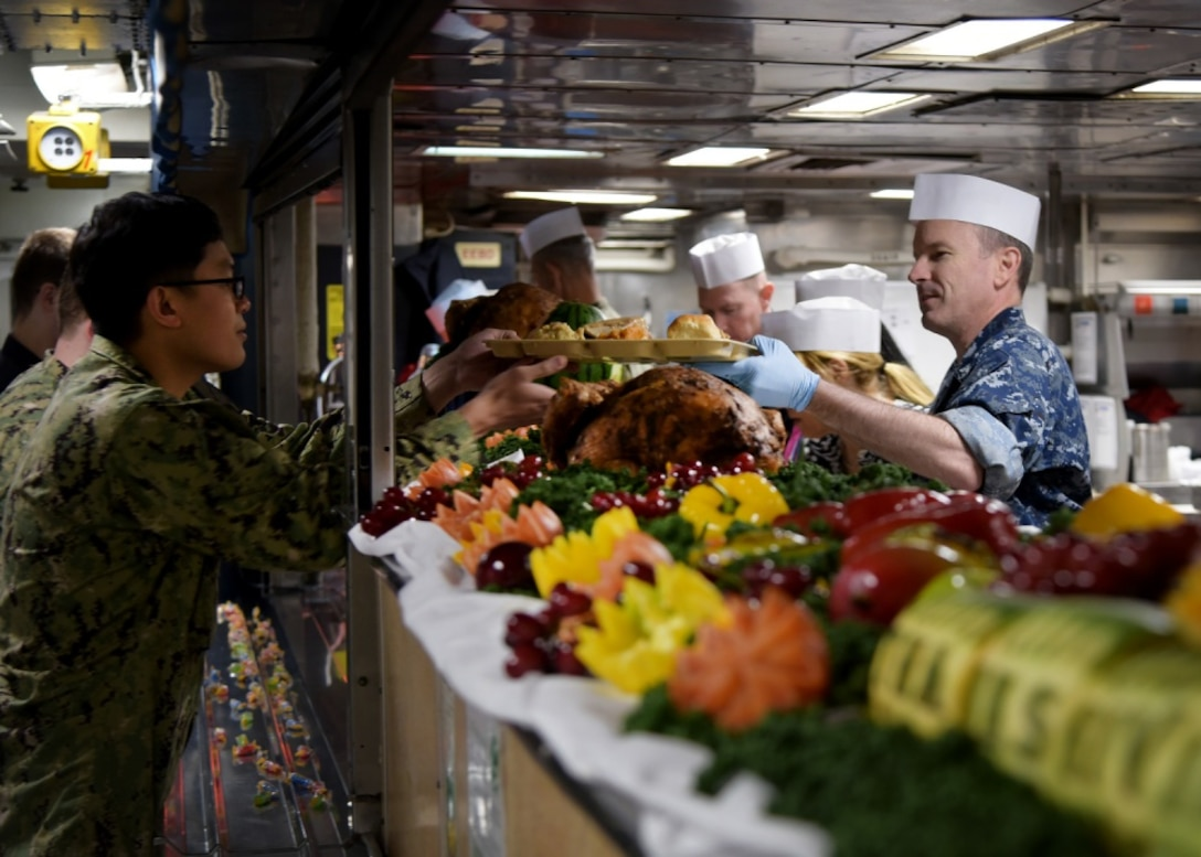 Capt. Colby Howard (right), commanding officer of the amphibious assault ship USS Wasp (LHD 1), serves a traditional Thanksgiving meal to sailors during a celebration aboard the ship forward deployed to Sasebo, Japan, Nov. 22, 2018. Each year, DLA Troop Support Subsistence supply chain employees ensure service members around the world get to enjoy a traditional Thanksgiving meal. (U.S. Navy photo by Mass Communication Specialist 1st Class Daniel Barker)