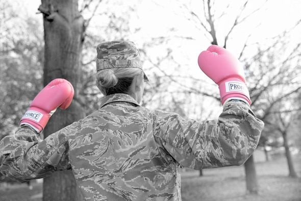 Black and white photo of a woman wearing an Air Force uniform and pink boxing gloves.