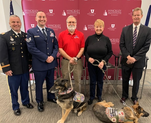 Five panelists and two military working dogs pose in front of a red University of Utah Hinckley Institute for Politics backdrop.
