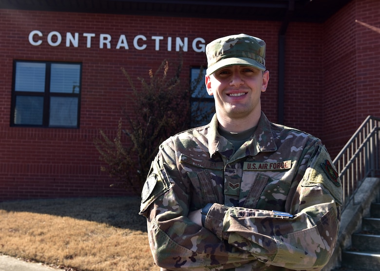 """A male in uniform stands outside next to a brick building with the words """"Contracting"""" written on the side"""