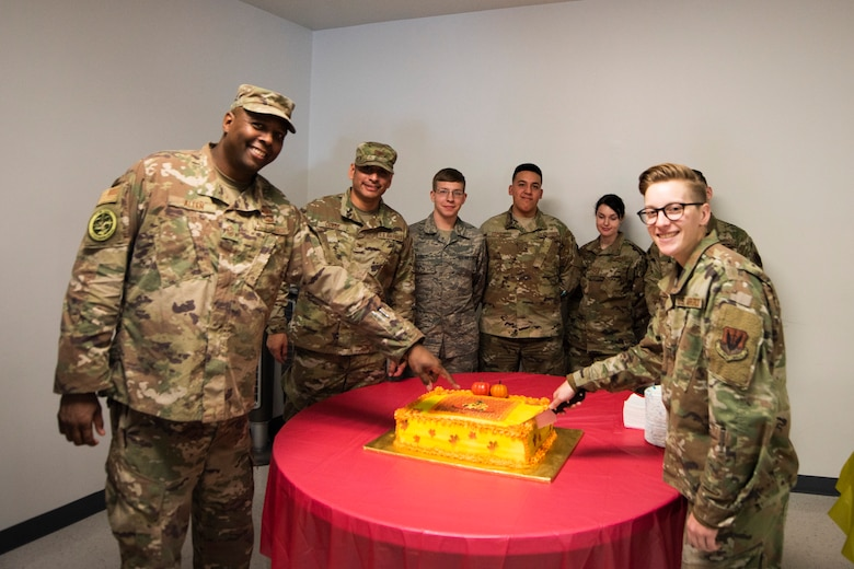 A photo of Airmen posing before cutting cake at the Annual Airman Thanksgiving Lunch