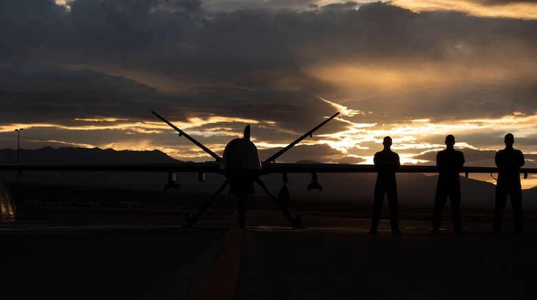 3 Airmen pose in front of an MQ-9 Reaper underneath a Nevada sunset.