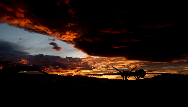 An MQ-9 Reaper sits on the flight line underneath a Nevada sunset.