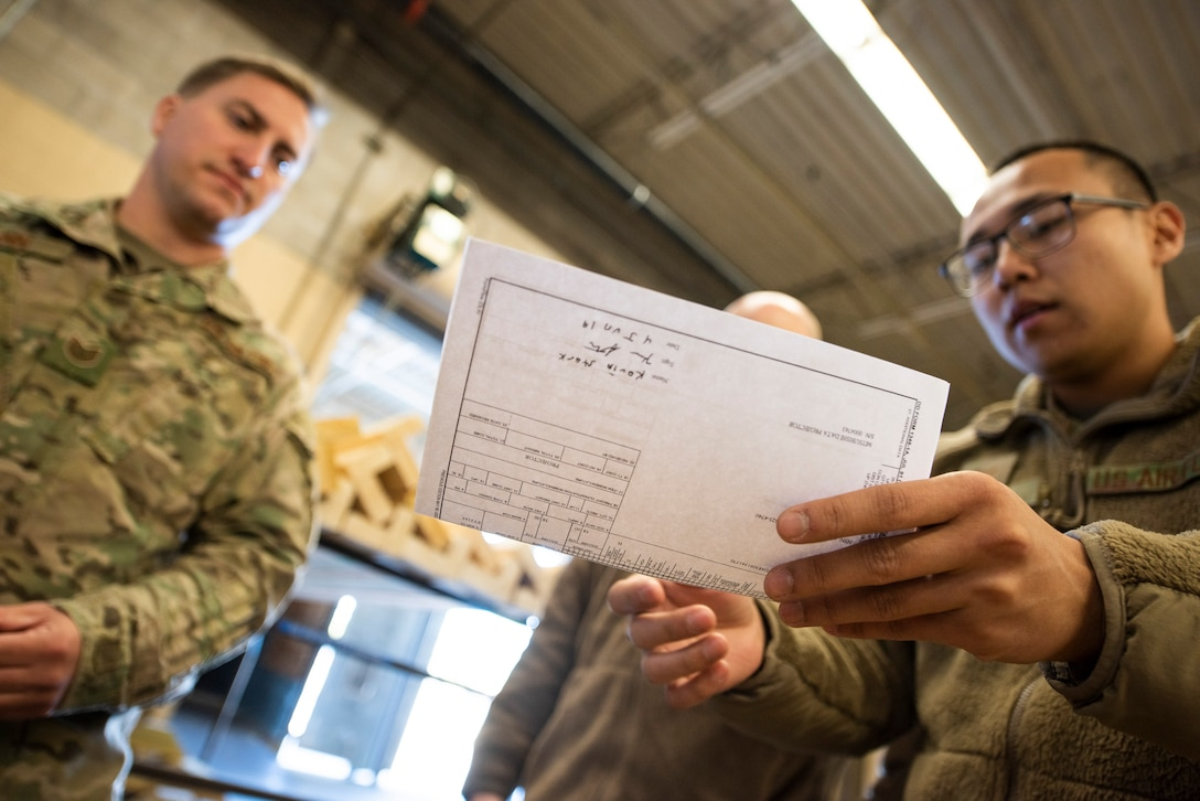 A photo of an Airman reviewing paperwork with another Airman.