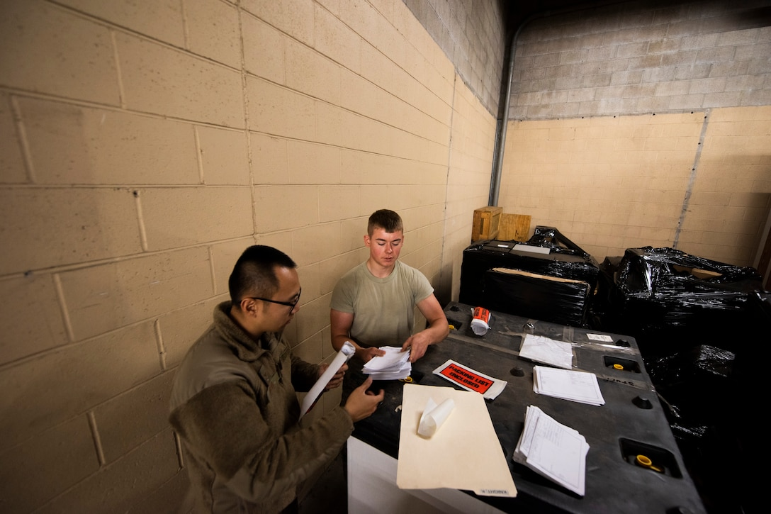 A photo of Airmen organizing shipment labels for old equipment.
