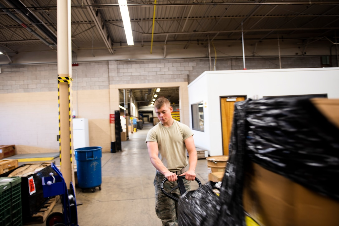 A photo of an Airman using a pallet jack to move heavy equipment.