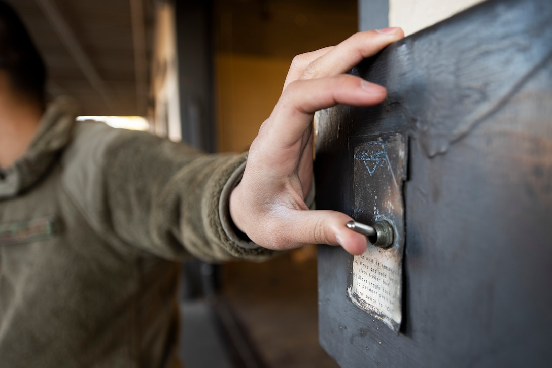 A photo of an Airman flipping a switch that controls a ramp.