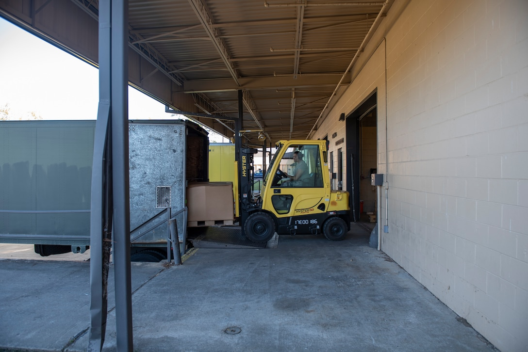 A photo of an Airman using a forklift to move a shipment into a truck.