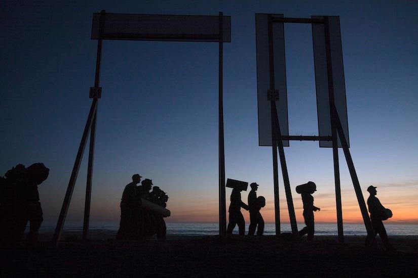 At dusk, service member in silhouette walk along a beach.