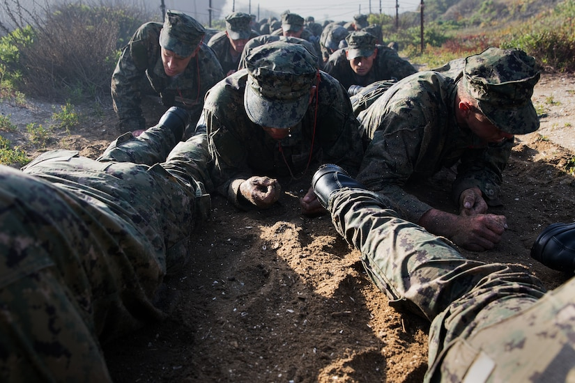A long line of service members crawl on their bellies through dirt.