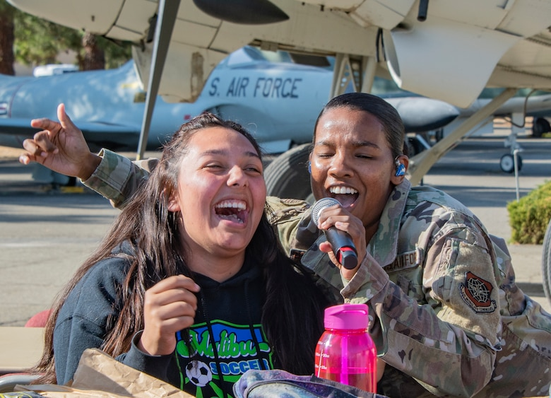 U.S. Air Force Senior Airman Salina Boodoosingh, a vocalist with the United States Air Force Band of the Golden West, motivates student participation during a performance Nov. 21, 2019, Travis Air Force Base, California. Travis AFB hosted Junior Reserve Officer Training Corps students from five Northern California high schools and one Oregon high school. The students learned about various U.S. Air Force career fields and toured static aircraft, the Heritage Center museum and dormitories. They also talked with Airmen about military life. (U.S. Air Force photo by Heide Couch)