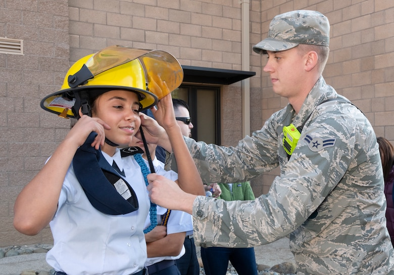 U.S. Air Force Airman 1st Class Cody Ferris, 60th Civil Engineer Squadron firefighter, helps a student try on a helmet during a base tour Nov. 21, 2019, at Travis Air Force Base, California. Travis AFB hosted Junior Reserve Officer Training Corps students from five Northern California high schools and one Oregon high school. The students learned about various U.S. Air Force career fields and toured static aircraft, the Heritage Center museum and dormitories. They also talked with Airmen about military life. (U.S. Air Force photo by Heide Couch)