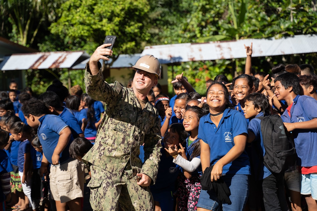 A sailor poses for a selfie with a group of students.