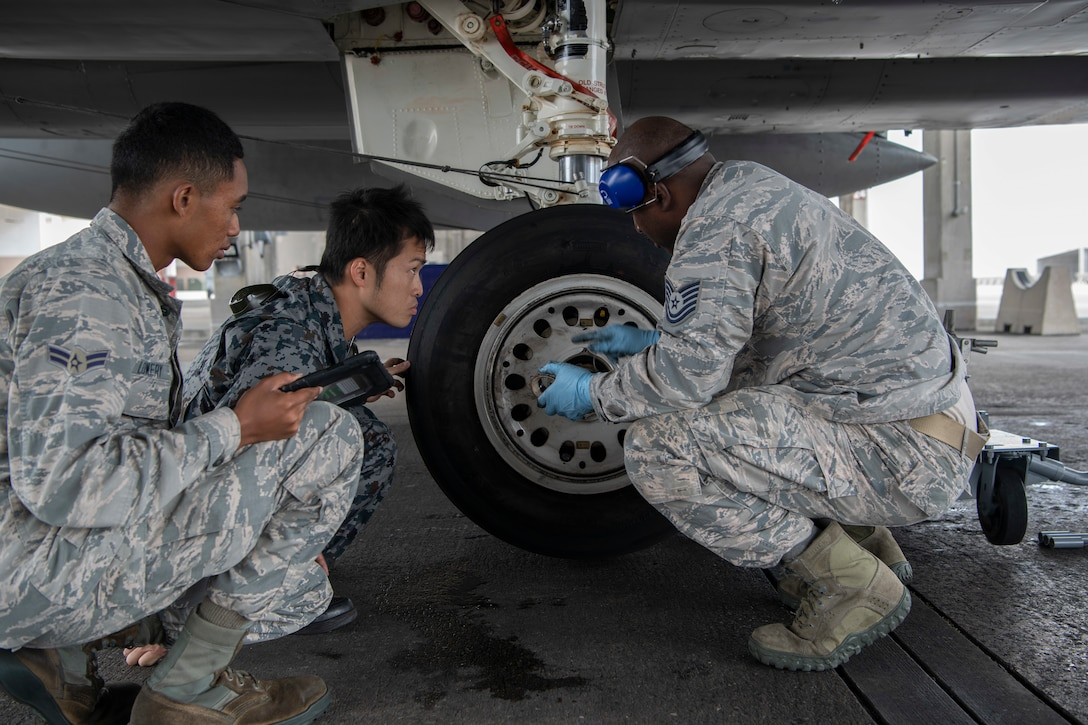 U.S. Air Force Airman 1st Class Christian Lowery, 18th Aircraft Maintenance Squadron crew chief, left, Japanese Self-Defense Force Staff Sgt. Shuichiro Masunaga, 6th Tactical Fighter Squadron aircraft general technician, middle, and U.S. Air Force Tech. Sgt. Adrian Lemard, 18th Aircraft Maintenance Squadron crew chief, right, train on changing tires on an F-15C Eagle as part of an NCO Bilateral Exchange program Nov. 19, 2019, at Kadena Air Base, Japan. Bilateral exchanges allow for a better understanding of the capabilities held by each countries Armed Forces, as well as the opportunity to improve relations between the United States and Japan. (U.S. Air Force photo by Senior Airman Rhett Isbell)