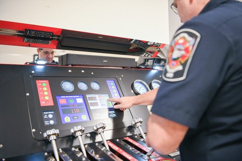 Jason Medina, Fire and Emergency Services driver operator, touches a digital screen on a pump simulator panel that is adorned with handles,dials and gauges.