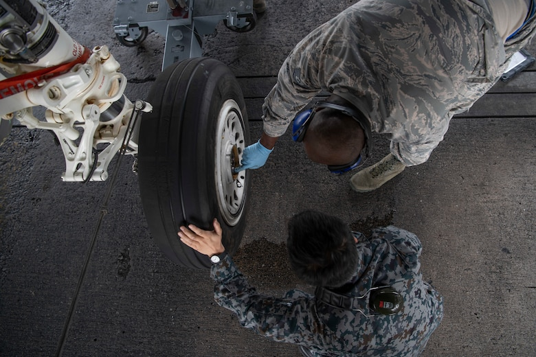 Japanese Self-Defense Force Staff Sgt. Shuichiro Masunaga, 6th Tactical Fighter Squadron aircraft general technician, left, and U.S. Air ForceTech. Sgt. Adrian Lemard, 18th Aircraft Maintenance Squadron crew chief, train on changing tires on an F-15C Eagle as part of an NCO Bilateral Exchange program Nov. 19, 2019, at Kadena Air Base, Japan. Bilateral exchanges allow for a better understanding of the capabilities held by each countries Armed Forces,as well as the opportunity to improve relations between the United States and Japan. (U.S. Air Force photo by Senior Airman Rhett Isbell)