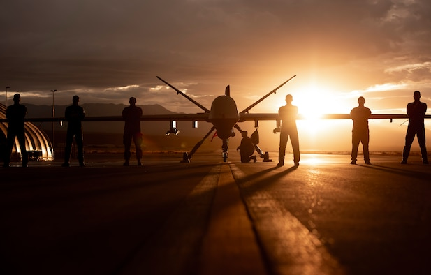 432nd Wing/432nd Air Expeditionary Wing Airmen pose in front of an MQ-9 Reaper underneath a Nevada sunset.