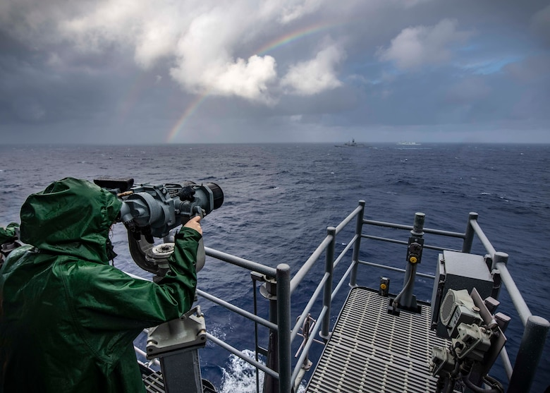 PHILIPPINE SEA (Nov. 21, 2019) Lt. j.g. Katherine Lindman, from Minneapolis, looks through binoculars on the bridge of the Ticonderoga-class guided-missile cruiser USS Chancellorsville (CG 62) during a group maneuvering exercise with ships from the Royal Australian Navy, Royal Canadian Navy, and Republic of Korea Navy as part of Pacific Vanguard 2019. Chancellorsville is forward-deployed to the U.S. 7th Fleet area of operations in support of security and stability in the Indo-Pacific region.