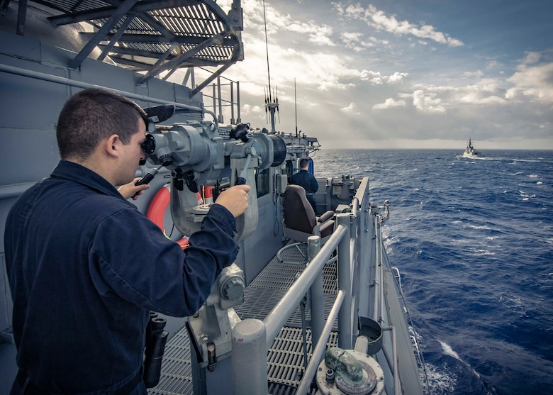 PHILIPPINE SEA (Nov. 21, 2019) Seaman Kevin Henriquez, from New Haven, Conn., looks through binoculars on the bridge of the Ticonderoga-class guided-missile cruiser USS Chancellorsville (CG 62) as the ship maneuvers behind the Royal Australian Navy ship HMAS Hobart (DDG 39) during a group maneuvering exercise with ships from the Royal Australian Navy, Royal Canadian Navy, and Republic of Korea Navy as part of Pacific Vanguard 2019. Chancellorsville is forward-deployed to the U.S. 7th Fleet area of operations in support of security and stability in the Indo-Pacific region.