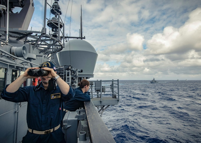 PHILIPPINE SEA (Nov. 21, 2019) Ens. Warren McWilliams looks forward as Lt. j.g. Katherine Lindman observes approaching ships on the bridge of the Ticonderoga-class guided-missile cruiser USS Chancellorsville (CG 62) during a group maneuvering exercise with ships from the Royal Australian Navy, Royal Canadian Navy, and Republic of Korea Navy as part of Pacific Vanguard 2019. Chancellorsville is forward-deployed to the U.S. 7th Fleet area of operations in support of security and stability in the Indo-Pacific region.