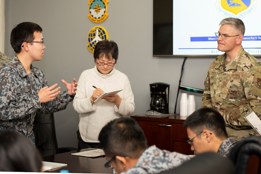 A Japanese Air Self-Defense Force Lieutenant, left, asks Col. Todd Wydra, 374th Maintenance Group Commander, right, a question after the initial briefing during a basic maintenance officer tour at Yokota Air Base, Japan, Nov. 21, 2019.