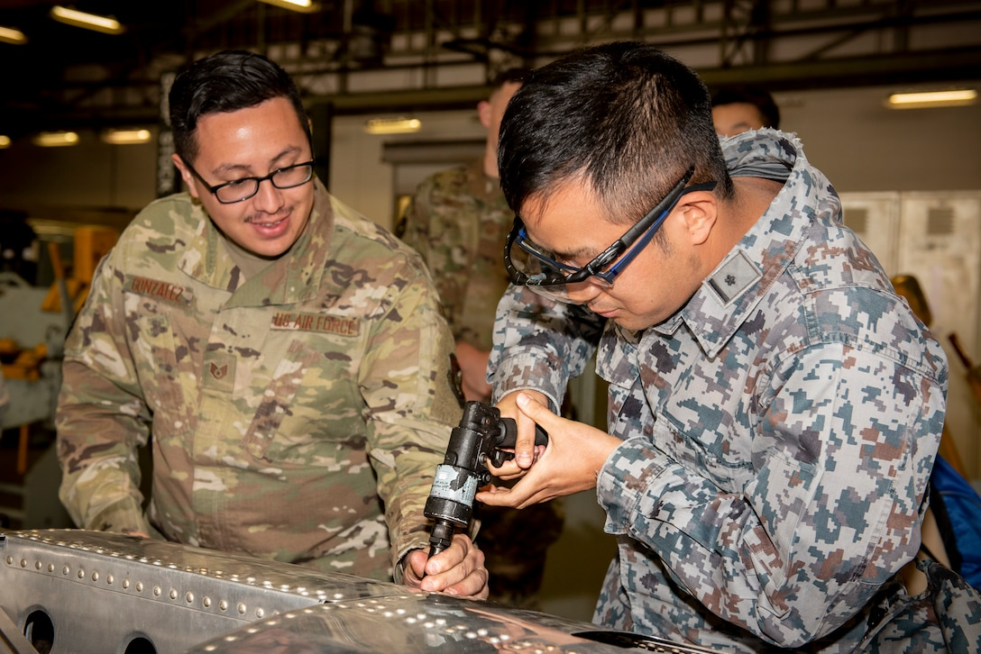 Staff Sgt. Llunas Gonzalez, 374th Maintenance Squadron aircraft structure maintenance craftsman, left, teaches a Japanese Air Self-Defense Force Lieutenant, right, how to use a rivet gun during a basic maintenance officer tour at Yokota Air Base, Japan, Nov. 21, 2019.