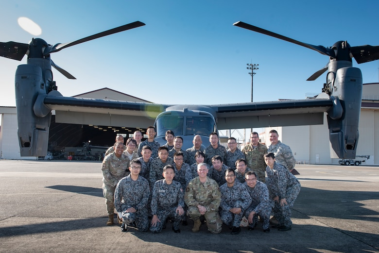 U.S. Air Force and Japanese Air Self-Defense Force members pose for a photo in front of a CV-22 Osprey during a basic maintenance officer tour at Yokota Air Base, Japan, Nov. 21, 2019.