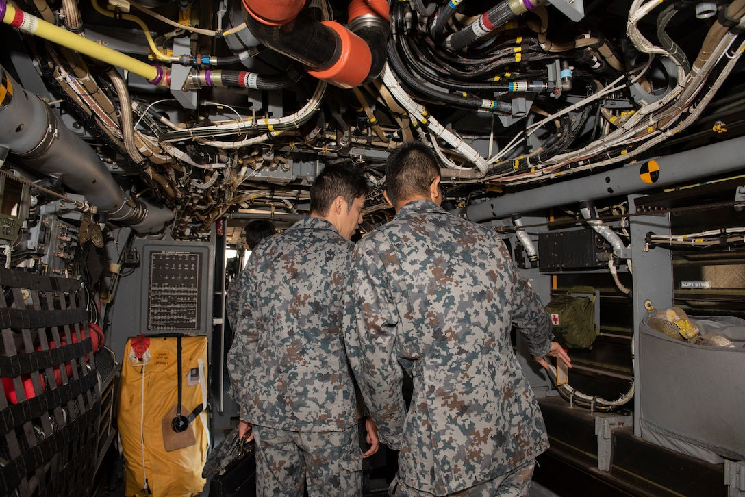 Japanese Air Self-Defense Force Lieutenants explore the inside of a CV-22 Osprey during a basic maintenance officer tour at Yokota Air Base, Japan, Nov. 21, 2019