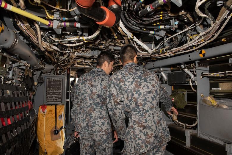 Japanese Air Self-Defense Force Lieutenants explore the inside of a CV-22 Osprey during a basic maintenance officer tour at Yokota Air Base, Japan, Nov. 21, 2019