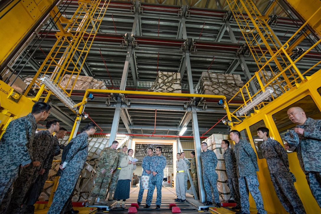 Tech.Sgt. Austin Kelley, 730th Air Mobility Squadron air freight shift supervisor, explains the capabilities of a Mechanized Material Handling System to Japanese Air Self-Defense Force Lieutenants during a basic maintenance officer tour at Yokota Air Base, Japan, Nov. 21, 2019.