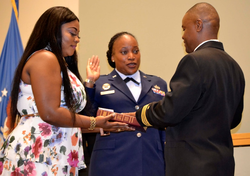 Naomi Tailey, left, wife of Navy Lt. Cmdr. Prince Tailey, right, stands beside Air Force Lt. Col. Chiriga Wilson, center, holding the Bible on which her husband reaffirms his oath of service during a promotion ceremony in his honor November 22, 2019, in Philadelphia.