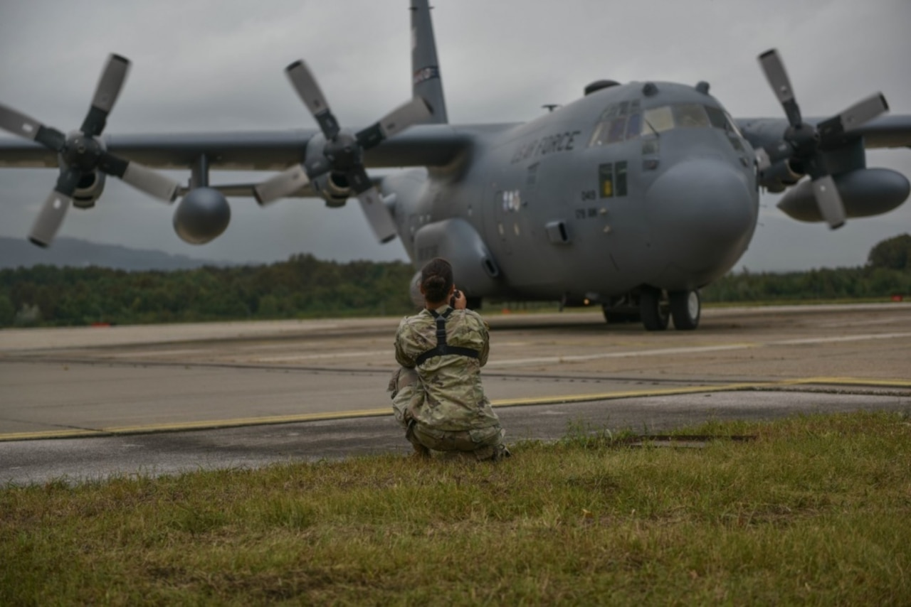 A soldier kneels on the tarmac to take photos of a C-130H Hercules aircraft.