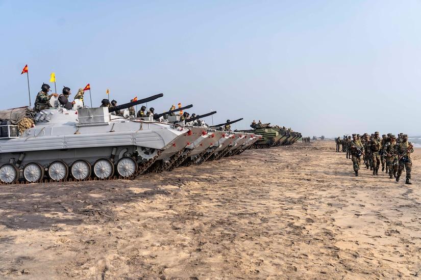 A group of Marines walk alongside a row of tanks.