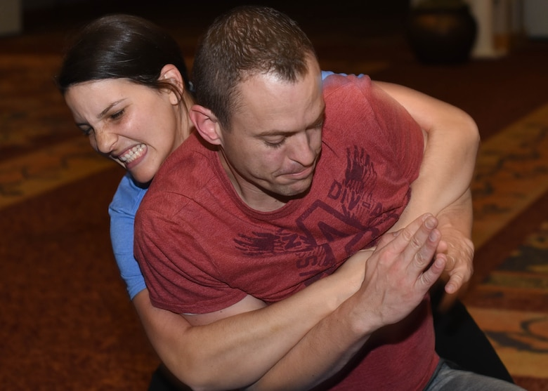 Kaycee Belka, 344th Air Refueling Squadron key spouse, grabs Capt. Jacob Belka, 344th ARS pilot, during a self-defense class Nov. 23, 2019, at McConnell Air Force Base, Kan. The 22nd Force Support Squadron plans on continuing classes once a month to help Team McConnell boost self-confidence and improve situational awareness. (U.S. Air Force photo by Airman 1st Class Alexi Bosarge)
