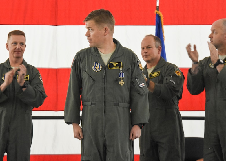 Maj. John Tice, a flight commander with the 303d Fighter Squadron, center, received the Distinguished Flying Cross and is recognized during a ceremony at Whiteman Air Force Base, Mo., Nov. 2, 2019. Tice was awarded for a mission he flew out of Kandahar Air Base, Afghanistan, in December 2010.