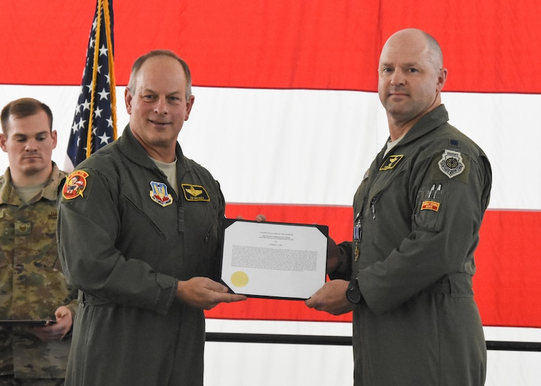 Retired Brig. Gen. Jim Mackey presents the Distinguished Flying Cross with Valor citation to Lt. Col. Anthony Roe, a flight commander with the 303d Fighter Squadron, during a ceremony at Whiteman Air Force Base, Mo., Nov. 2, 2019. Mackey and Roe deployed to Afghanistan in 2008 and flew the mission together that earned Roe his third Distinguished Flying Cross.