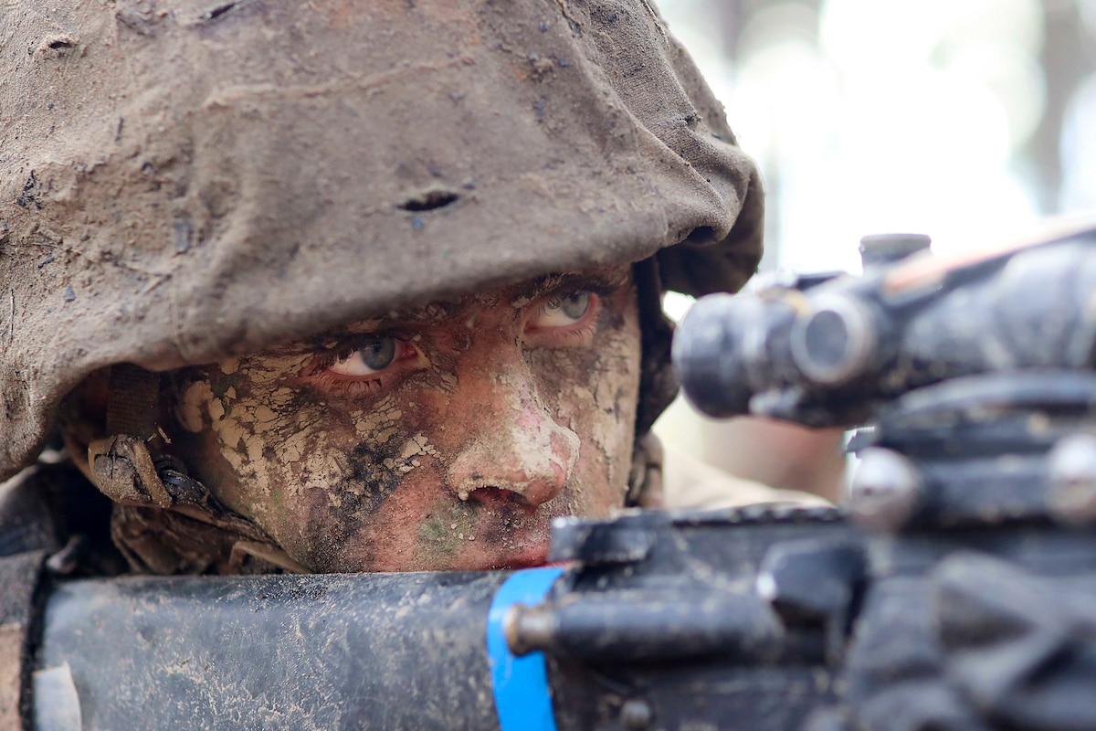 A Marine Corps recruit looks through a view finder on a weapon.