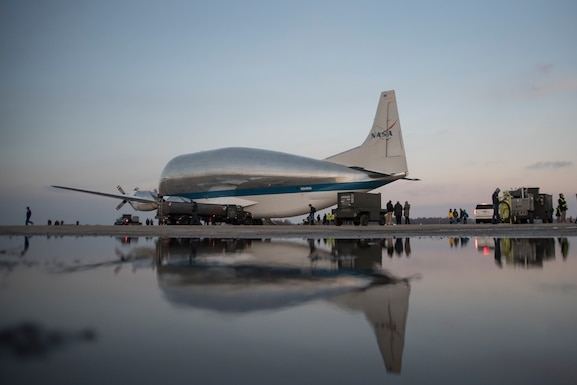 A photo of the NASA Super Guppy aircraft and it's reflection, parked on the flight line after a snow shower melted