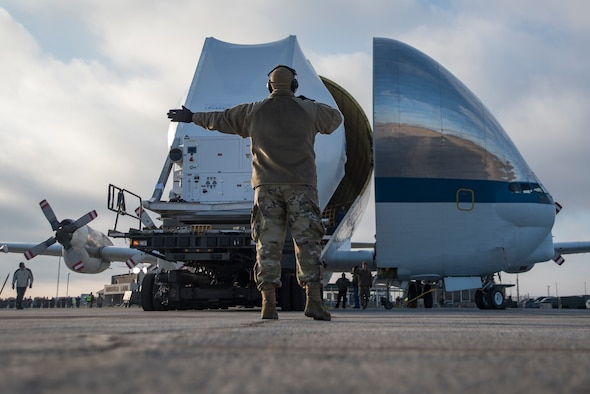 A photo of the back of a 179th Airlift Wing military member directing the off-loading process, as he stands in front of the NASA Super Guppy