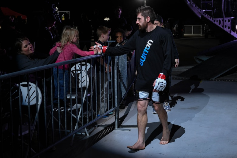 Nelson Tuckwiller, Cage Fury Fighting Championship fighter, interacts with a fan before his fight during the CFFC 80 at Joint Base Langley-Eustis, Virginia, Nov. 22, 2019.