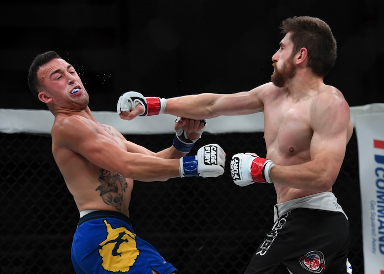 "Nelson Tuckwiller punches Joshua Lilley during the Cage Fury Fighting Champion 80 ""Fight for Troops"" event at Joint Base Langley-Eustis, Virginia, Nov. 22, 2019."