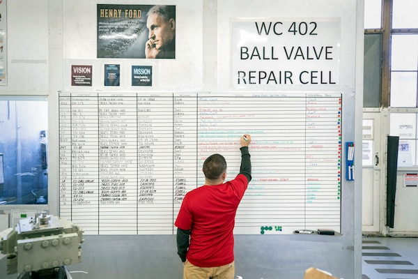 Romel Ramos, a bench mechanic with Shop 31, Inside Machine Shop, updates the status board for employees with Work Center-402 inside Building 432.