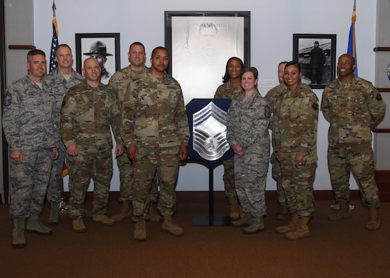 Chiefs from McConnell Air Force Base, Kan., pose with the newest Chief Master Sgt. selects Nov. 26, 2019. There were four Senior Master Sergeants chosen to promote to the rank of Chief, two of the selects were deployed. (U.S. Air Force photo by Airman 1st Class Alexi Bosarge)