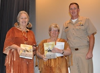 """IMAGE: DAHLGREN, Va. (Nov. 21, 2019) - Capt. Casey Plew, Naval Surface Warfare Center Dahlgren Division (NSWCDD) commanding officer, presents the Dahlgren history book, """"The Sound of Freedom,"""" to Twila Bradley and Minnie Lightner, guest speakers at the NSWCDD sponsored National American Indian Heritage Month Observance at the base theater. Bradley and Lightner – members of the Patawomeck Indian Tribe of Virginia – spoke about the culture, history, and contributions of the Patawomeck Tribe in terms of the heritage month's 2019 theme: """"Honoring Our Nations: Building Strength Through Understanding"""".  (U.S. Navy photo/Released)"""
